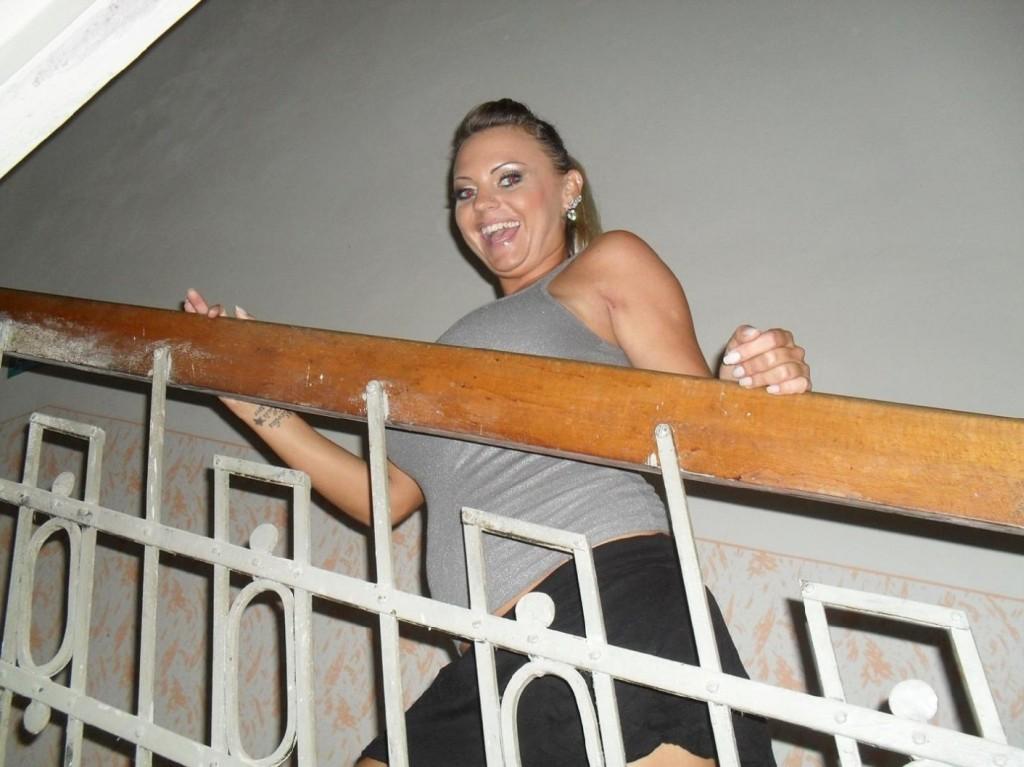 Vollbusige Blondine schaut fröhlich vom Treppengeländer herunter
